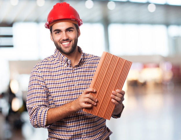 Worker man with brick Free Photo