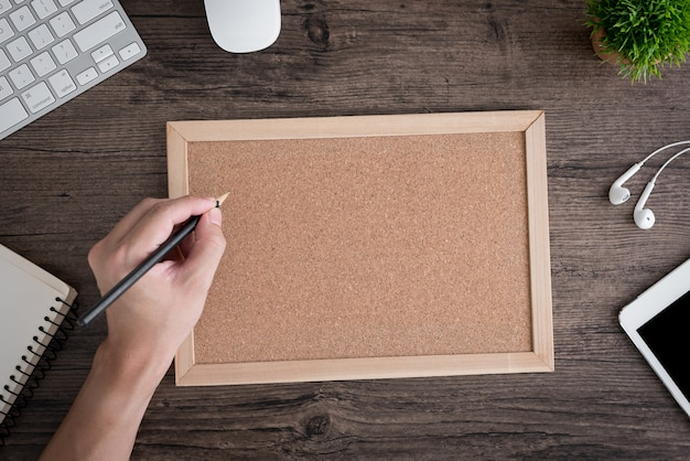 Worker at the office writing on cork board Premium Photo