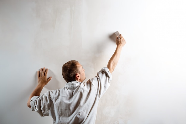 Worker painting wall with brush in white color. Free Photo