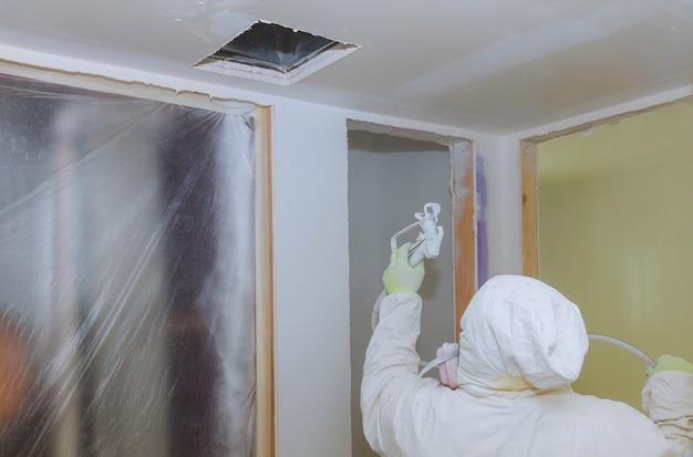 Рабочий красит стену распылителем в белый цвет. Premium Фотографии