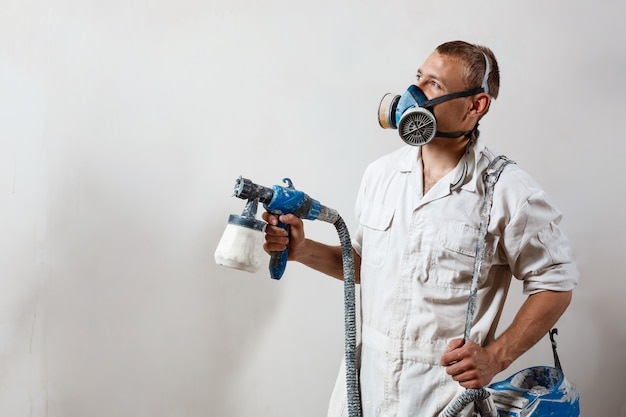 Worker painting wall with spray gun in white color. Free Photo