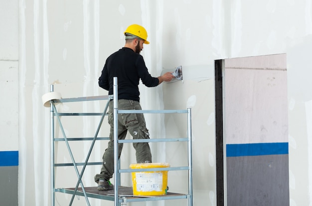 Worker plastering gypsum board wall. Premium Photo