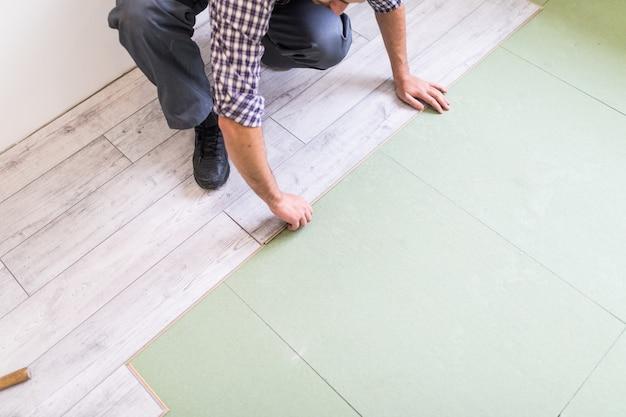 Lavoratore che elabora un pavimento con assi del pavimento laminato luminoso Foto Gratuite