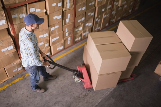 Worker pushing trolley with boxes in warehouse Premium Photo