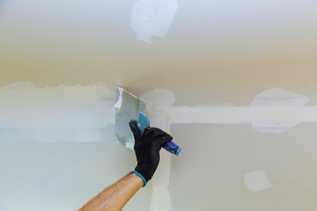 Worker puttied wall using a paint spatula Premium Photo