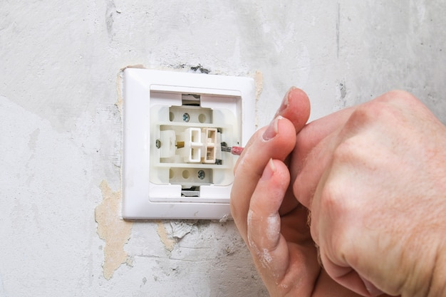 A worker removes the light switch for wallpapering. Premium Photo