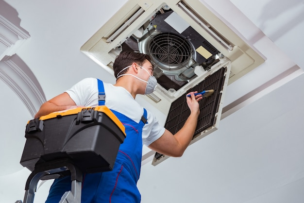 Worker repairing ceiling air conditioning unit Premium Photo