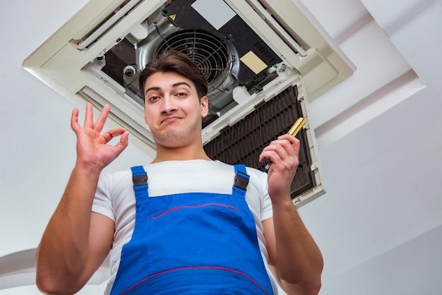 Worker repairing ceiling air conditioning unit Premium Photo