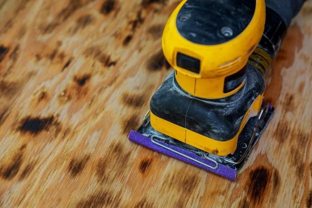 Worker sander to sand wood Premium Photo