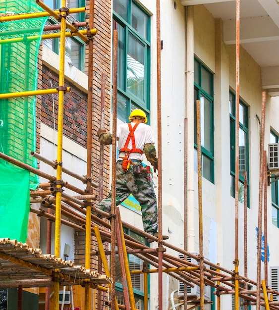 Worker on scaffolding repairing the building. Premium Photo