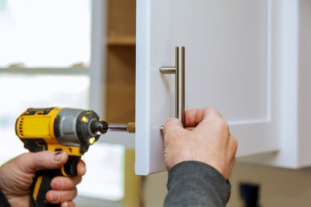 The worker sets a new handle on the white cabinet with a screwdriver Premium Photo