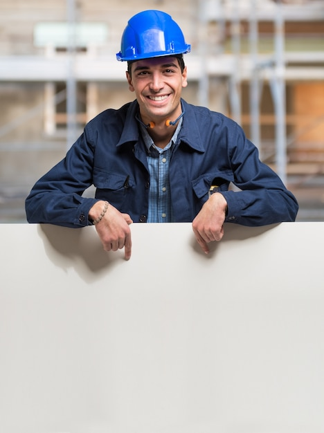Worker showing a white sign in a construction site Premium Photo