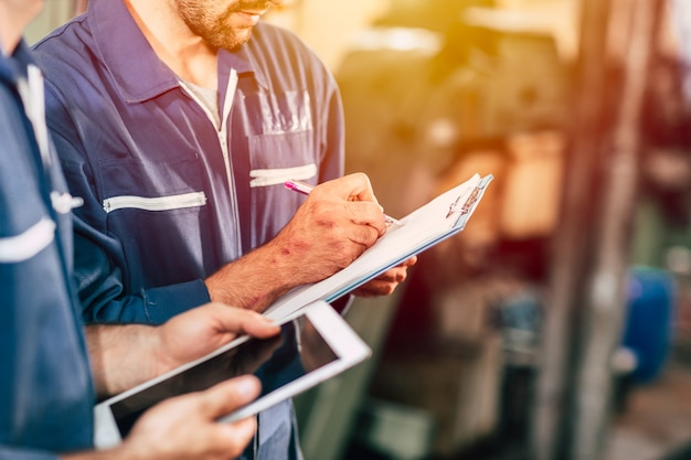 Worker taking note using pen and paper with new young engineer using computer tablet for work faster and more efficiency. Premium Photo