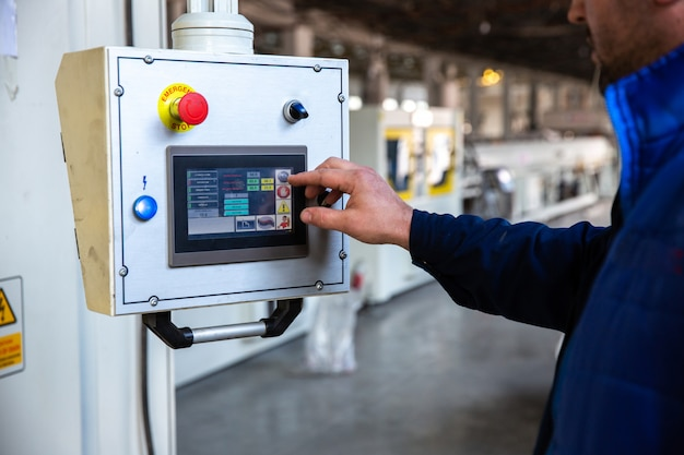 Il lavoratore utilizza il pannello di controllo in fabbrica Foto Gratuite