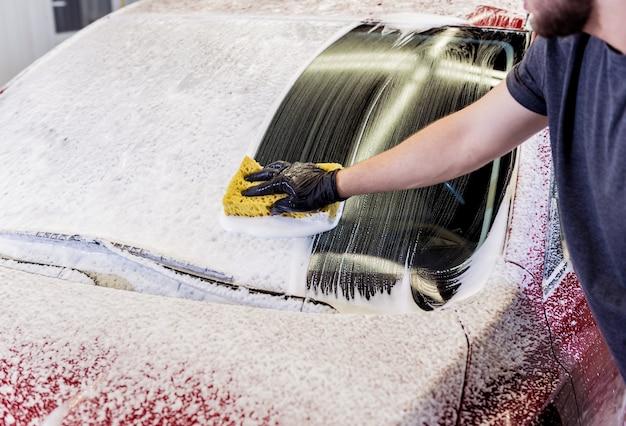 Рабочий моет красный автомобиль губкой на автомойке. Premium Фотографии