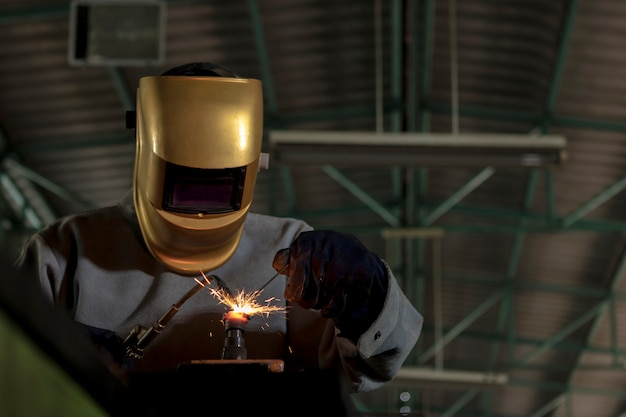 Worker welder working welding gas steel in industry with safety mask gloves and safety equipment. Premium Photo