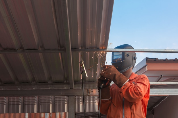 Worker welding in orange work clothes welding for roof truss Premium Photo