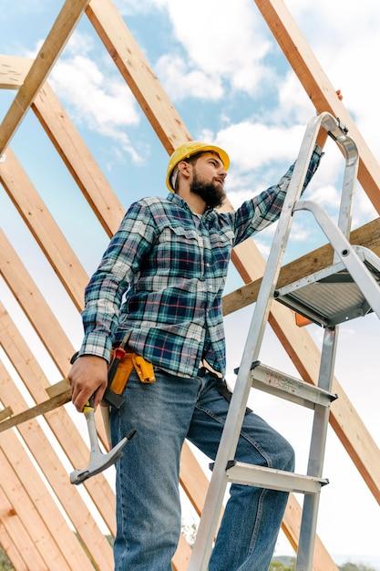 ヘルメットとハンマーで家を建てる労働者 無料写真