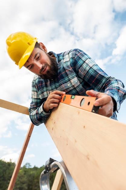 ヘルメットとレベルが屋根材をチェックしている労働者 無料写真