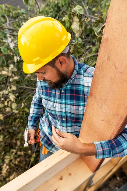 木でヘルメットの建物を持つ労働者 無料写真