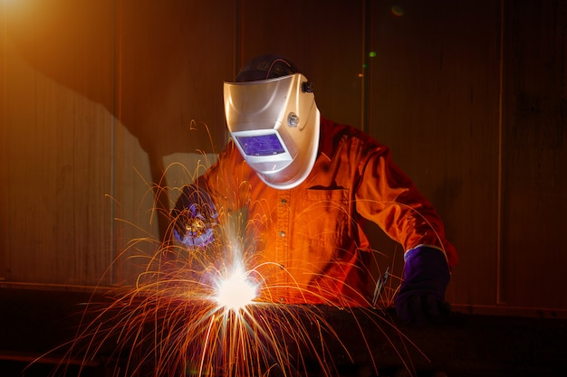 Worker with protective mask welding metal in warehouse industrial. Premium Photo