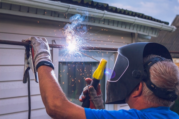 Worker with welding machine performs work Premium Photo