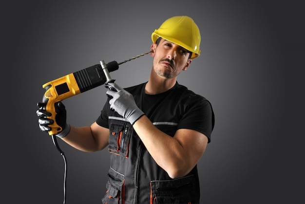 Worker with yellow helmet, drill and hammer Premium Photo