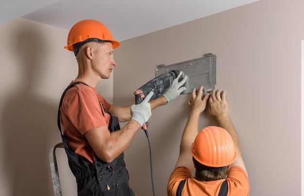 Рабочие устанавливают сплит-систему для домашней системы кондиционирования воздуха. Premium Фотографии