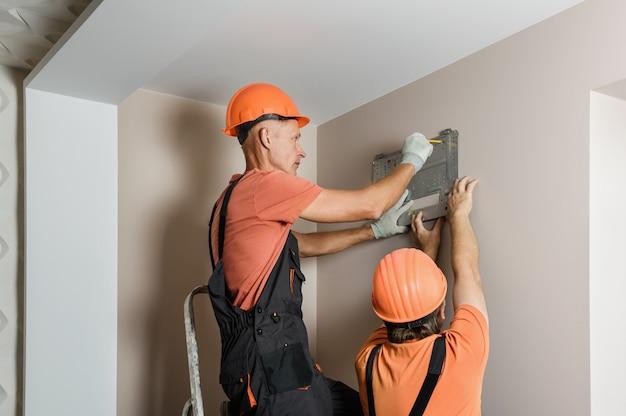Рабочие устанавливают сплит-систему домашнего кондиционера. Premium Фотографии