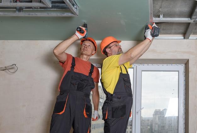 Рабочие с помощью отверток прикрепляют гипсокартон к потолку. Premium Фотографии