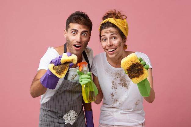 サービスクリーニングの労働者は、スポンジでほこりを拭き取ります。洗剤で家を掃除する幸せな主婦と驚いた表情で夫 無料写真