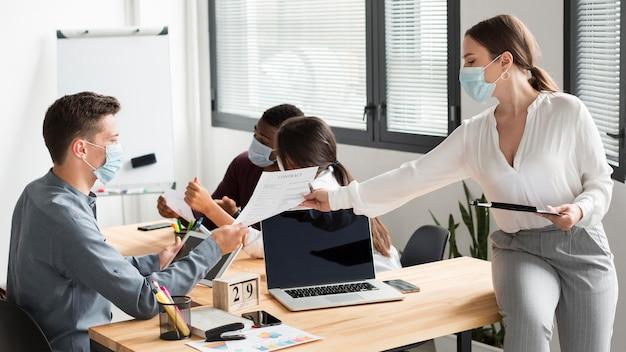 Рабочие в офисе во время пандемии в медицинских масках Бесплатные Фотографии