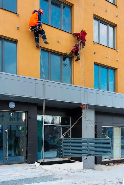Рабочие устанавливают ниши для кондиционеров на строящемся доме Premium Фотографии