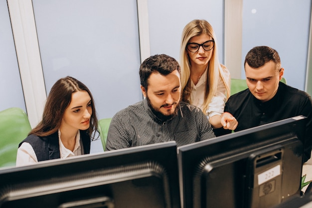 Workers at an it company working on a computer Free Photo