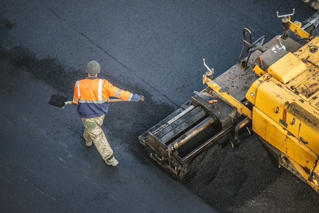Workers lay a new asphalt coating using hot bitumen. work of heavy machinery and paver. top view Premium Photo