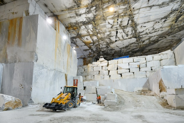 Workers and machinery inside a marble quarry or open cast mine during excavation of the white stone