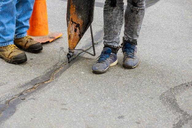 労働者は、道路のシーリングクラック道路建設のピットに液体アスファルトを噴霧することにより、舗装の軽微な修理を行います Premium写真