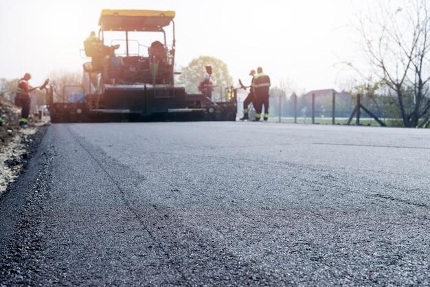 道路にアスファルトの新しいコーティングを配置する労働者 無料写真