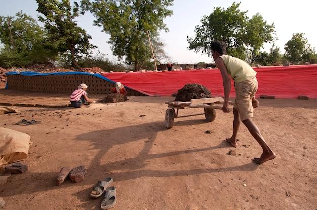 レンガ工場で伝統的なレンガを作るために粘土で処理する労働者 Premium写真