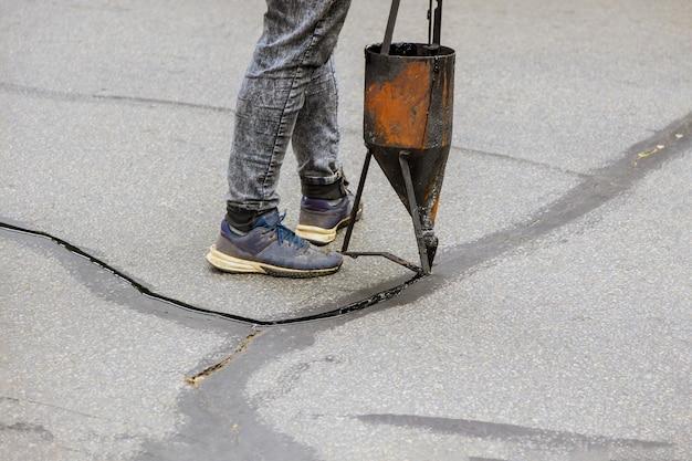 道路の道路保護コートをアスファルトに塗布する液体シーラーを適用して亀裂を封鎖する労働者の修復作業 Premium写真