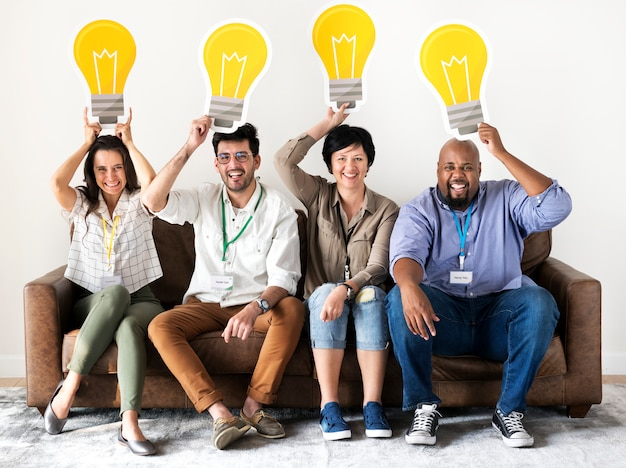 Workers sitting and holding light bulb icons Premium Photo