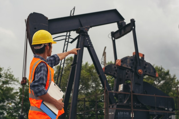 Workers standing and checking beside working oil pumps. Free Photo