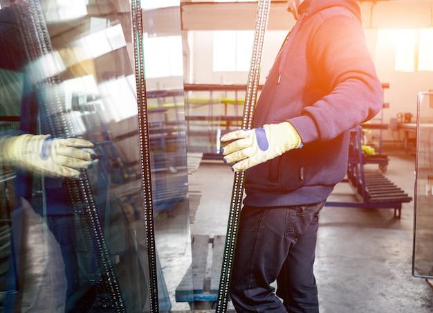 노동자들은 유리를 옮깁니다. 창문 및 문 생산 공장에서 프리미엄 사진
