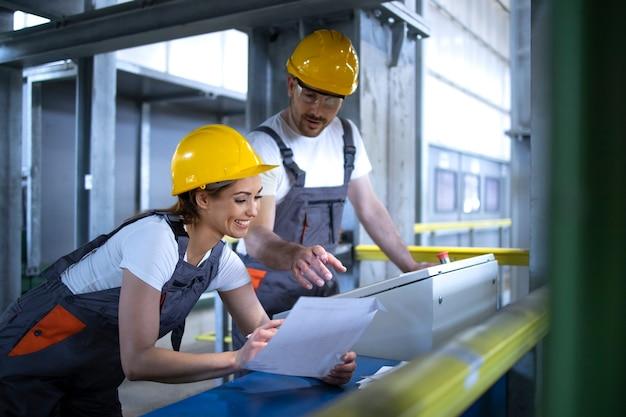 Lavoratori in divisa e macchine operatrici elmetto protettivo sul computer centrale della fabbrica Foto Gratuite