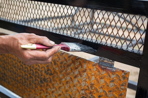 Workers use black steel paint brushes. Free Photo