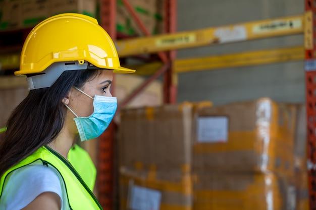 倉庫でcovid-19から保護するために防護マスクを着用している労働者。 Premium写真