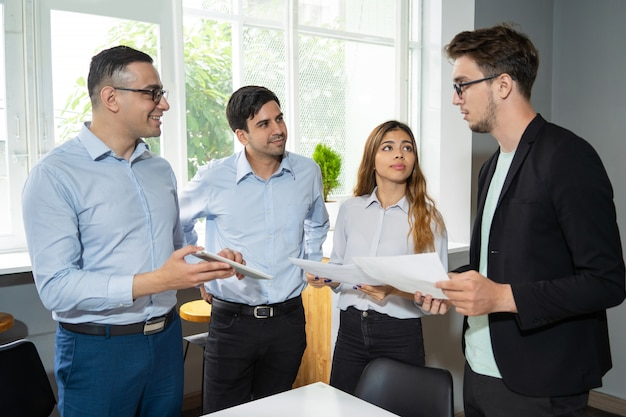 Workgroup of three reporting to serious young team leader Free Photo