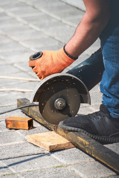 Working hands cuts off a metal pipe with angle grinder Premium Photo