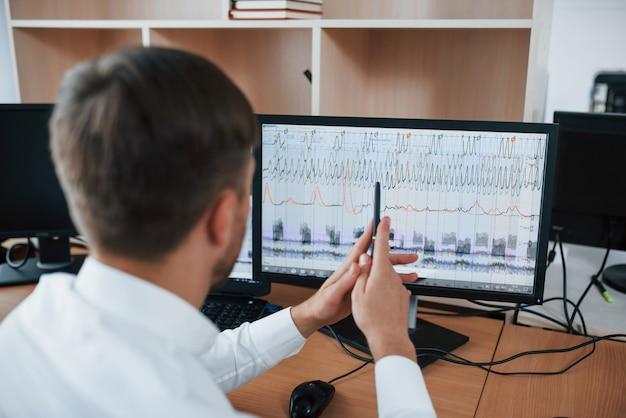 Processo lavorativo. esaminatore di poligrafo in ufficio con la sua attrezzatura da macchina della verità Foto Gratuite
