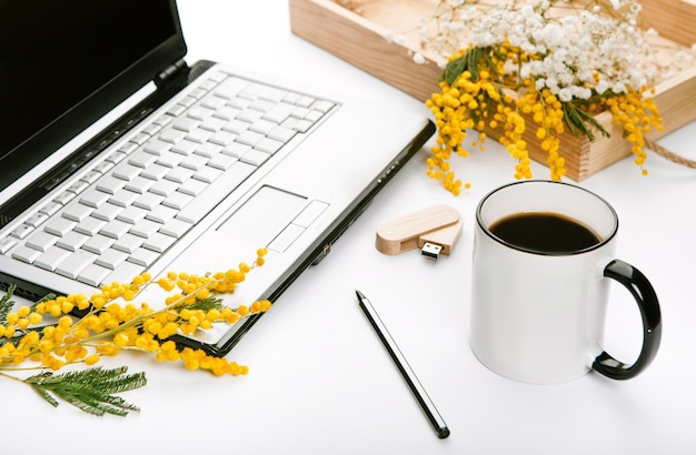 Working set for spring holidays with flowers and office laptop flash drive Free Photo